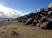 Red and white boulders form a barrier against the encroaching tide.